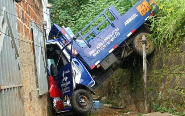 Caminhão fica 'pendurado' entre casa e ribanceira