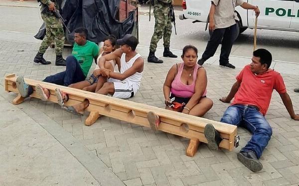 Cidadãos são presos pelos pés por desrespeito à quarentena, na Colômbia