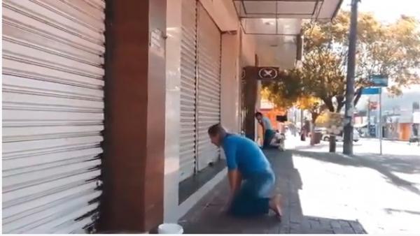 Ajoelhados diante das lojas fechadas, comerciantes clamam a Deus por ajuda